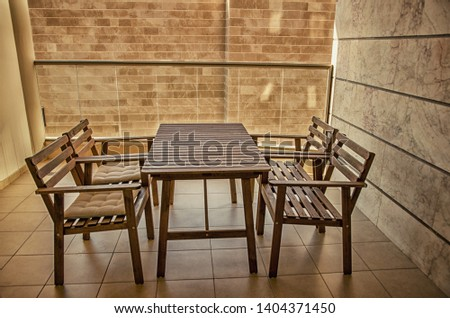 There are a wooden table and four chairs on a balcony with a close-up view of the neighboring building, exactly close enough to have touched it. It may cause mental instability of dwellers.