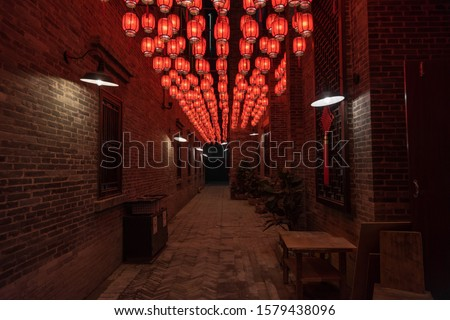 There are beautiful red lanterns hanging in Chinese festival alleys.Text translation on lantern: Blessing, Ancient Chinese characters of various blessings, auspicious, Safety