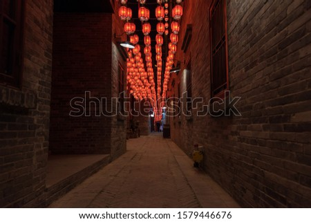 There are beautiful red lanterns hanging in Chinese festival alleys.Text translation on lantern: Blessing, Ancient Chinese characters of various blessings