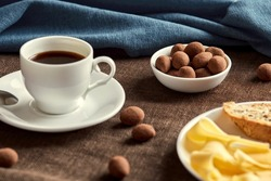 There are chocolates in a small plate. The plate is on a brown napkin. In front of the plate are a cup of coffee and a large plate of cheese and bread. Several chocolates scattered across the table.