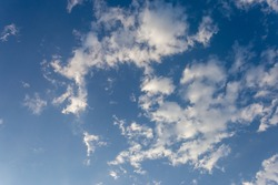 There are many beautiful floating white clouds and clear blue sky with light shining through the clouds. Sky images for blue background design make you feel fresh and bright.