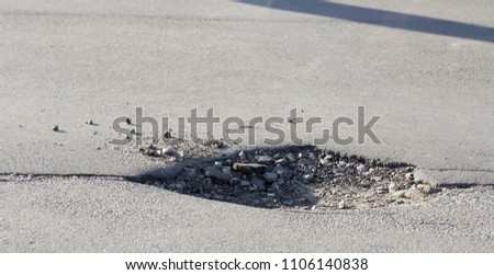 there are many potholes on the roadway close up