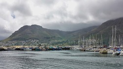 There are many sailing boats and ships in the bay. City buildings on the shore. The peaks of the coastal ridge are hidden in dense dark clouds and fog. False Bay. Cape Town. South Africa