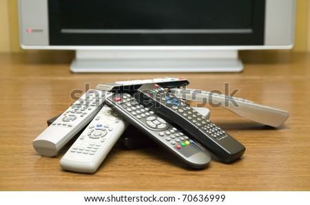 There are many tv controllers near televisor