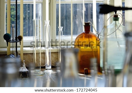 There are measuring cylinders, large bottles, glass flasks, metal support and bulbs  on the table in the chemical laboratory.