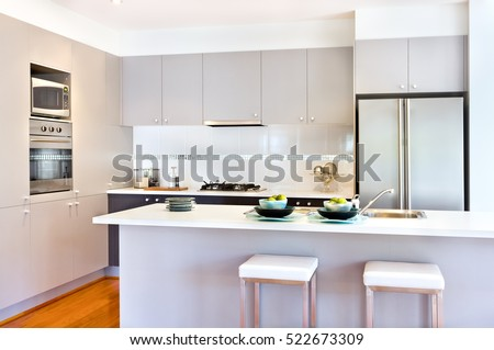 There are more wall cabinets or pantry cupboards with a stove and oven middle of it. The counter top is white next to the fridge, there are two small chairs in front of the counter.