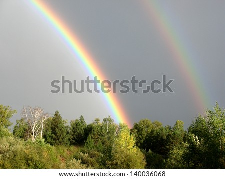 There are rainbow, cloudy sky and forest