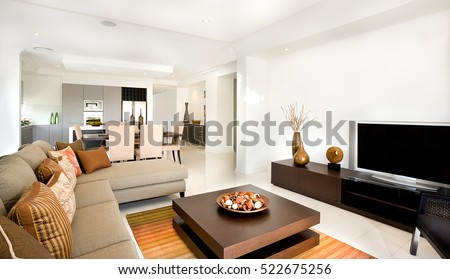 There are sofas and chairs with pillows in the modern living room including a creative wooden table with ornaments items on it. Long cupboard or TV stand with a vases close to the white wall,
