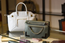 There are two handbags on a glass shelf in the store. One bag is green or khaki, the second bag is white. They are made of leather.