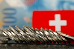 There are various Swiss coins visible against background of one hundred francs banknote and there is Swiss flag as well