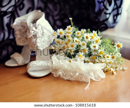 there are white wedding sandals with camomiles and a garter for the bride