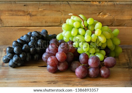 There different kinds of Grapes: green grape, red grape, dark grape on wooden background