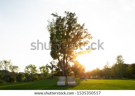 There is a bench under a big tree. The background is the sunset sky. #1535350517