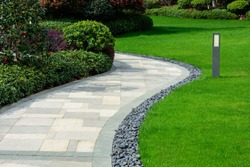 There is a black stone garden on the edge of the curved path, and the landscape lamp is on the green lawn.