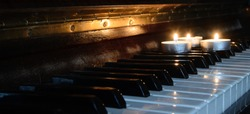 There is a burning candle on the piano keys. Concept - an evening of memories, performance of music.