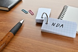 There is a card with the word of NDA which is an abbreviation for Non-Disclosure Agreement on the desk with paper clips, a pen and notebook.