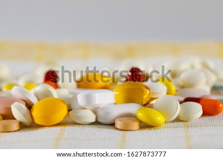 There is a large dose of pills on the napkin. These varied tablets have various shapes and various colors.