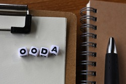 There is a notebook, a pen, and a clipboard with cubes formed OODA written on it. It was an abbreviation for Observe,Orient,Decide,Act.