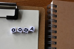 There is a notebook, and a clipboard with cubes formed OODA written on it. It was an abbreviation for Observe, Orient, Decide, Act.