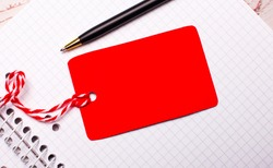 There is a pen and a red-colored price tag on a string with a place to insert text on a white notebook.
