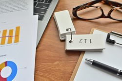 There is a piece of paper with a graph printed on it, a clipboard, and an open vocabulary book on the desk. The word CTI is there. It's an acronym that means Computer Telephony Integration.