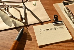 There is a piece of paper with the word Job description on the desk with a glasses and clipboard.