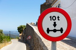 There is a red and white traffic sign at the roadside in Spain. A maximum axle load of 8 tons is permitted. In the background the Andalusian landscape blurred with bokeh.