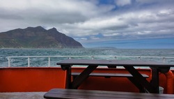 There is a table and benches on the deck of the ship. Outside the turquoise Atlantic Ocean and mountains on the shore are visible. There are dense cumulus clouds in the blue sky. South Africa.