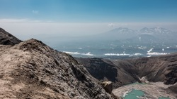 There is a turquoise acid lake in the crater of the volcano. The snow is melting on the banks. High steep slopes. Mountains with snow-covered slopes are visible against the blue sky. Kamchatka.Gorely