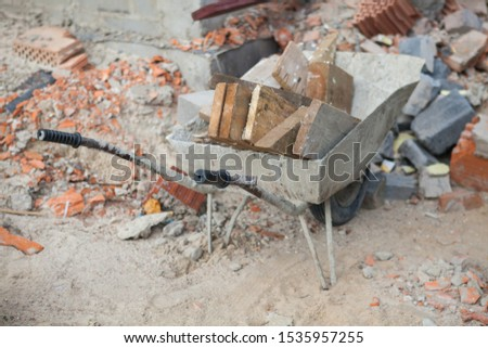 There is a wheelbarrow filled with wooden boards on the construction site #1535957255
