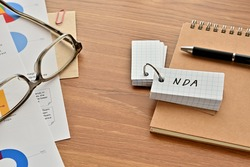 There is a word book with the word of NDA which is an abbreviation for Non-Disclosure Agreement on the desk with papers of graphs(with dummy text), a pen and glasses.