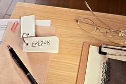 There is a word book with the word of PMBOK which is an abbreviation for Project Management Body Of Knowledge on the desk with a clipboard, a pen and glasses. (With dummy paper)