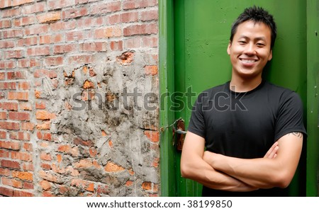 There is an Asian man stand against a old door and smile.