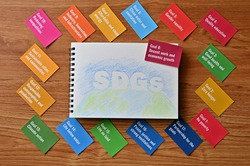 There is card with the statement Goal 8:Decent work and economic growth . It is one of the goals of the SDGs with sketch book.