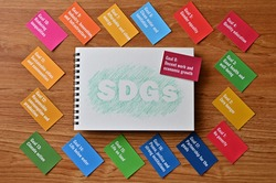 There is card with the statement Goal 8:Decent work and economic growth. It is one of the goals of the SDGs with sketch book.