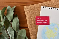 There is card with the statement Goal 8: Decent work and economic growth  on it one of the goals of the SDGs and a illustration of the earth.
