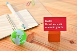There is card with the statement Goal 8:Decent work and economic growth on it one of the goals of the SDGs with earth ball.