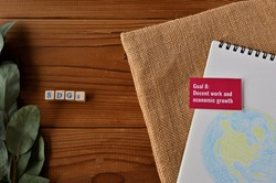 There is card with the statement Goal 8:Decent work and economic growth on it which is one of the goals of the SDGs. It is beside with a illustration of the earth and stamped wood cube.