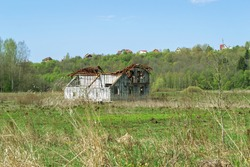 There is dry grass in the foreground. On the middle plan on the green field is an old, destroyed house. In the background is a hill with rural houses.