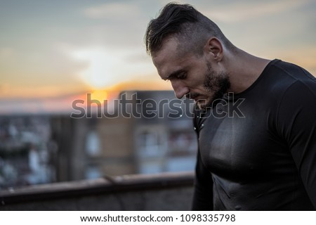 There is no success without sweat. Young handsome man training hard and sweating. Man doing sports outside on the bridge. Outdoors recreation, stretching and training fit body
