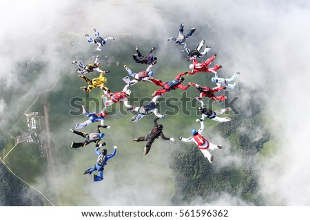 There is skydiving formation in the sky. All skydivers had already gripped each other, but one skydiver in the top left corner is only trying to do it.