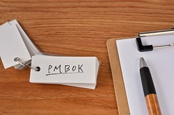 There's a clipboard, a pen and a notebook with a sticky note stuck to it that says PMBOK.