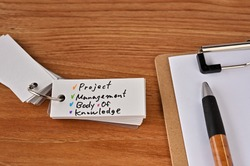 There's a clipboard, a pen and a notebook with a sticky note stuck to it that says Project Management Body of Knowledge.