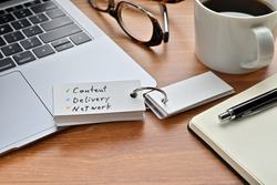 There's a laptop computer, a notebook, a pen and an open vocabulary book on the desk. The word Content Delivery Network is written on it.