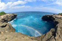 There's a rainbow over the sea looking down from the cliffs. Devils tears on rembongan island