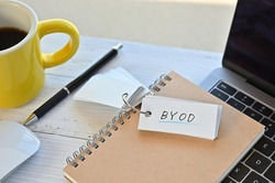 There's a word book on a desk with a cup of coffee and laptop pc. The word BYOD is written in it. It's an abbreviation for Bring Your Own Device.