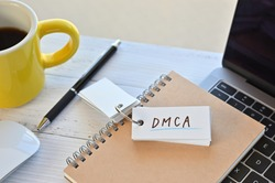 There's a word book on a desk with a cup of coffee and laptop pc. The word DMCA is written in it. It's an abbreviation for Digital Millennium Copyright Act.