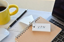 There's a word book on a desk with a cup of coffee and laptop pc. The word VPN is written in it. It's an abbreviation for Virtual Private Network.