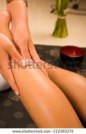 Thereapist hands massaging a female thigh