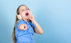 Theres a song for every emotion. Adorable amateur karaoke song singer on blue background. Cute small child doing vocal on song. Little girl singing song playing in headphones, copy space.